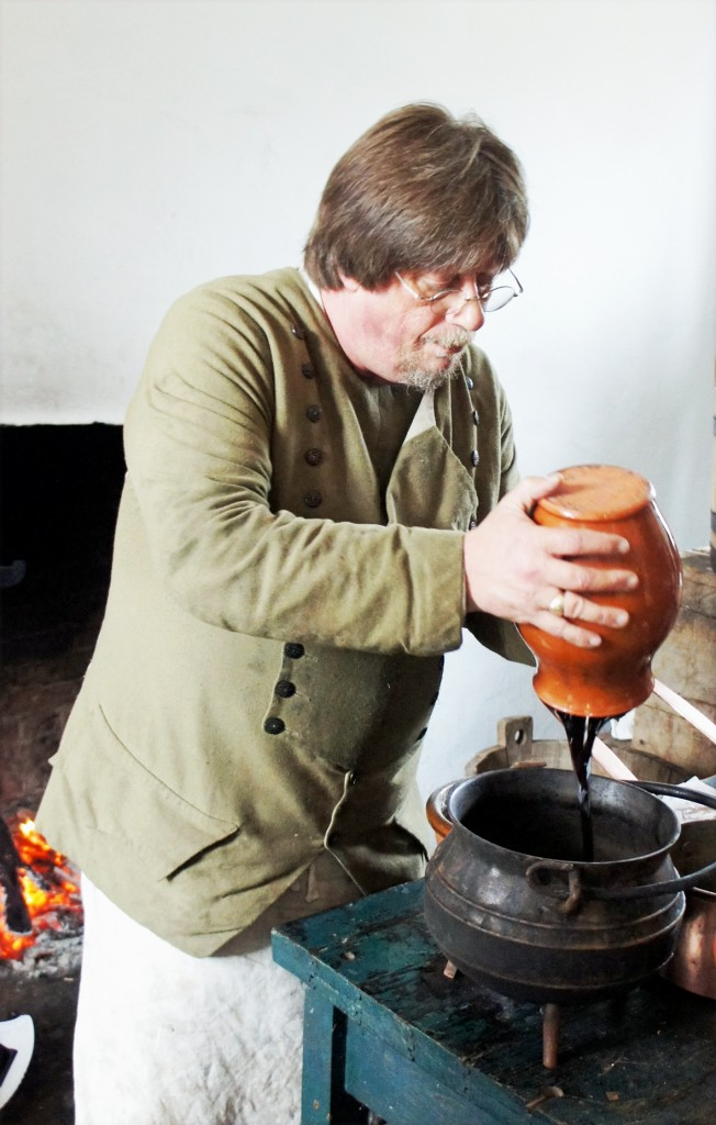 Addng the molasses to the iron pot before heating it to make essentia binae, porter colouring. (This was illegal for commercial brewers, but fine for home brewers)
